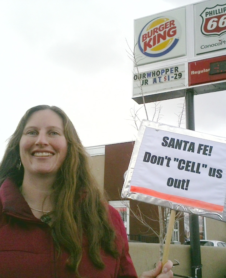 Protester Lynette Kennard directs her modest message to the passers while corporate logos blare from on high.