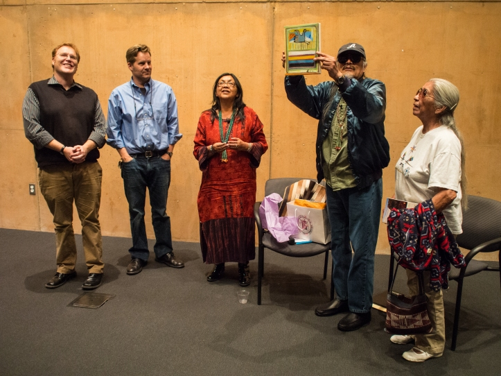 The keynote interview concluded when American Studies faculty and event organizers (left to right) Alyosha Goldstein, David Correia, and Jennifer Denetdale present John Redhouse and his wife Carol with gifts. Redhouse holds up a sand art painting from fellow activist/scholar Larry Emerson. On the chair is a Navajo-style rug woven by American Studies graduate student Venancio Aragon.