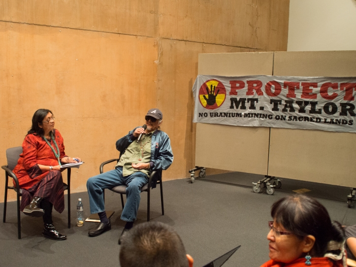 American Studies Associate Professor Jennifer Denetdale interviews Dine' activist and community organizer John Redhouse in front of a packed house. The conversation focused primarily on Redhouse's influence on Dine' and Indigenous scholarship and activism and the ongoing liberation and decolonization struggles of which he remains an important figure. They sit in front of a banner announcing MASE's (Multicultural Alliance for a Safe Environment) opposition to uranium mining at Mt. Taylor.