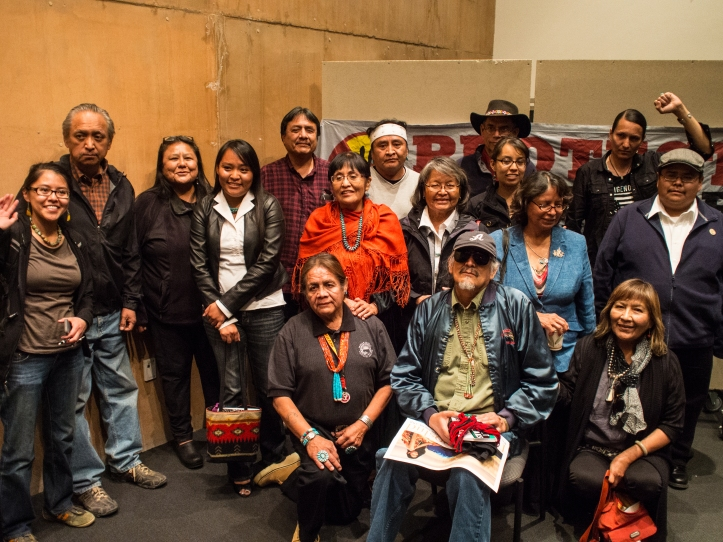 Many of the Dine' and Indigenous activists, scholars, and community leaders who attended Friday's event to honor the life and work of John Redhouse  gather around John at the conclusion of the program.