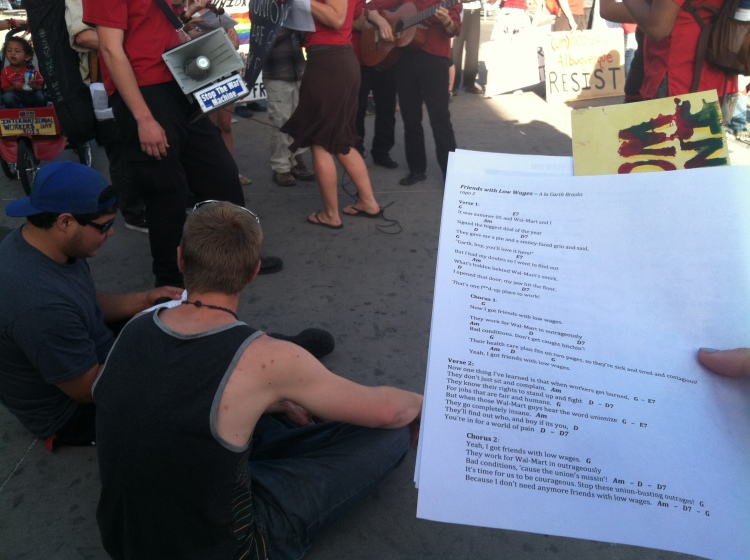 "One marcher holds the lyrics to ""I've got friends with low wages"" as the rally serenades Wal-Mart"