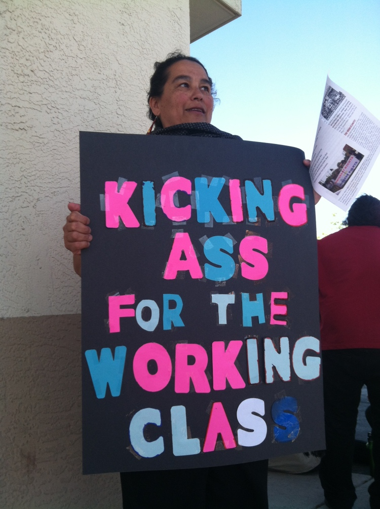 Maria Brazil, one of the march organizers with (un)Occupy and La Raza Unida, holds her home-made sign.