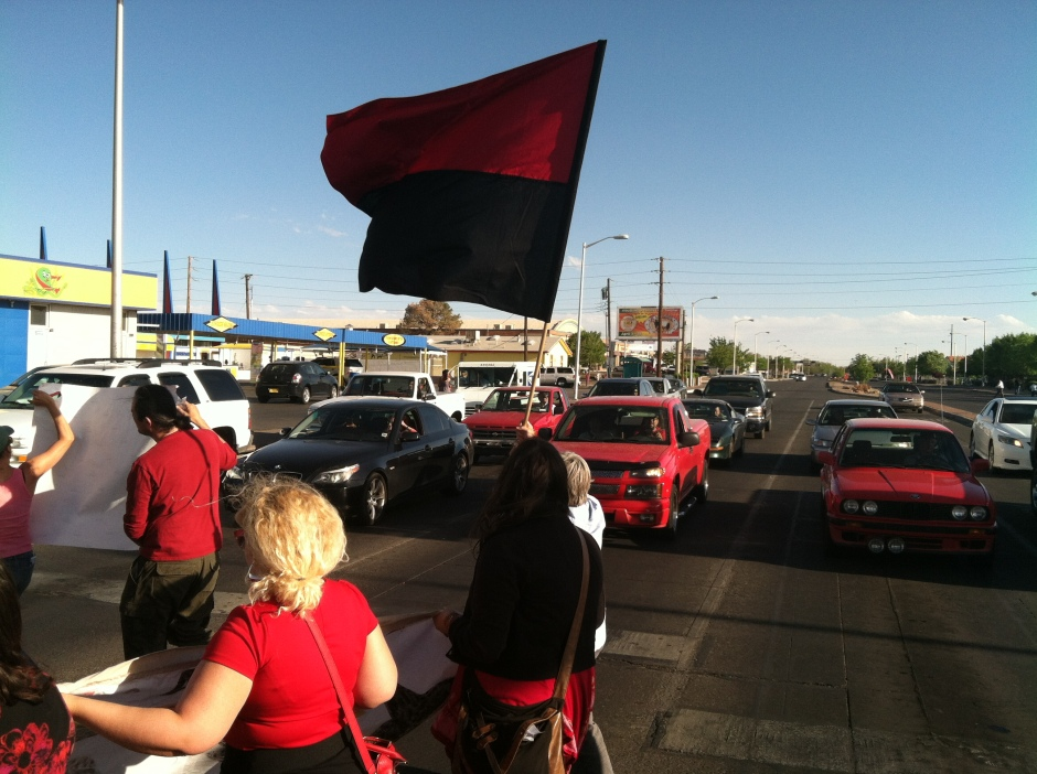 Nearly all of the marchers wore the familiar anarchist red and black colors. Strong winds during the march ensured that the Black and Red Flag waved prominently throughout the march.