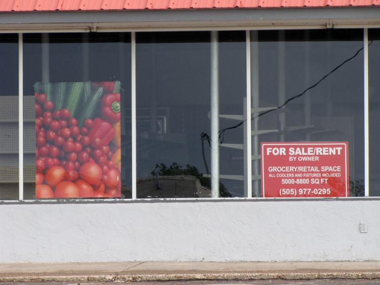 An empty grocery store for rent or sale by the owner.
