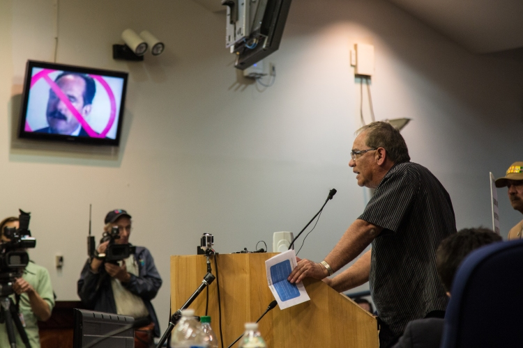 "Mike Gomez, pointing to the picture of Barry, said, ""This guy has to go."" He reminded councilors that this was not the first time people have brought grievances to the City Council about out of control police violence and murders. Exasperated, Gomez told councilors, ""You don't even listen to us."""