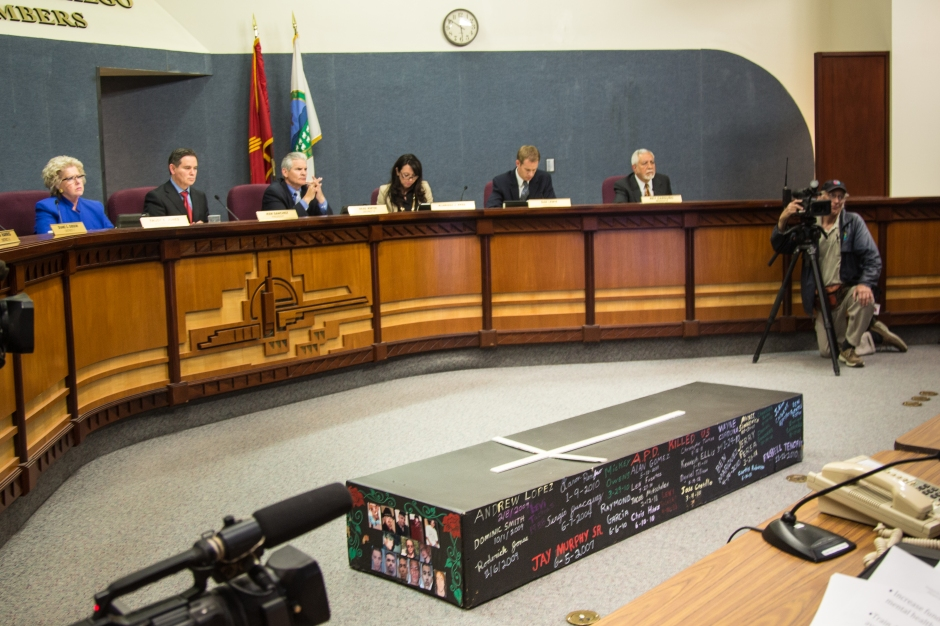 A black coffin with the names and pictures of the 23 people killed by APD since 2010 laid at the feet of the councilors as the listened to public testimony.