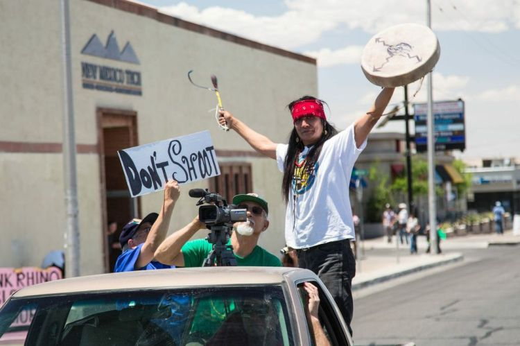 """A marcher holds his hands up next to a sign that says, """"Don't Shoot."""""""