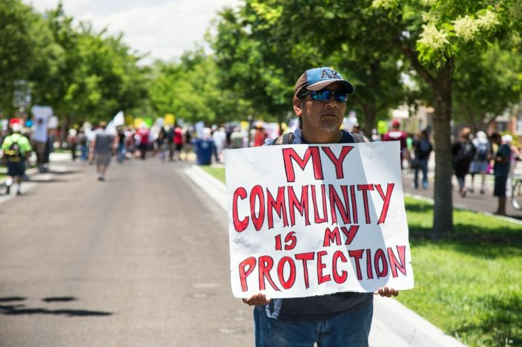 "A protester at the rear of the march holds a sign that says, ""My community is my protection."" The people at Saturday's march represented all walks of life in Albuquerque, since APD police violence is not specific to one group of people but to the community in general."