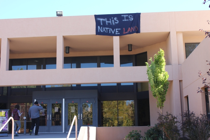 Banners were quickly removed by UNM staff. The one above was dropped above the entrance to the Johnson Center.