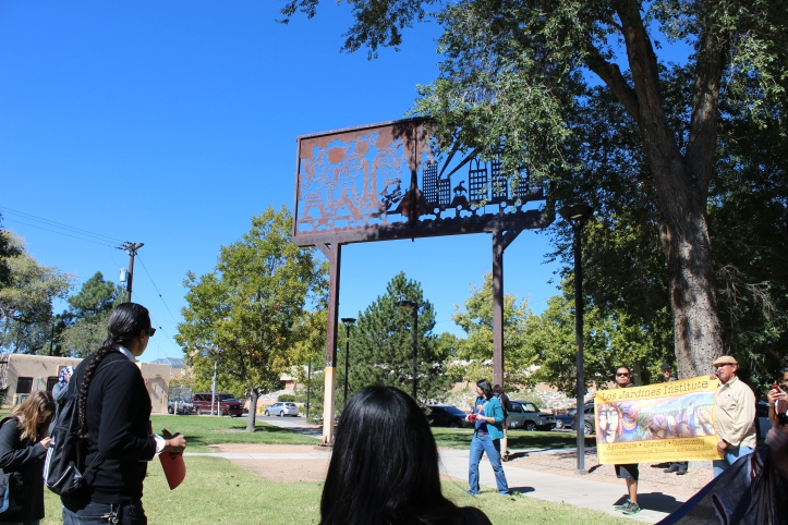 "Yale Park was the first stop on the tour. Estes told the marchers that the  massive billboard sculpture called ""Cultural Crossroads of America"", which depicts the collision of Native peoples and European colonizers, is ""one of the few places on campus that celebrates indigenous land here in Albuquerque.""  When Chiricahua Apache artist Bob Haozous first revealed his sculpture in 1997, he included a line of concertina, or barbed-wire, along the top of the sculpture. UNM refused to pay Haozous until he agreed to remove the wire. According to some Anglo critics, the concertina wire drew in too sharp a relief the violence of settler colonialism suggested in Haozous's sculpture. The wire was removed in 1998."