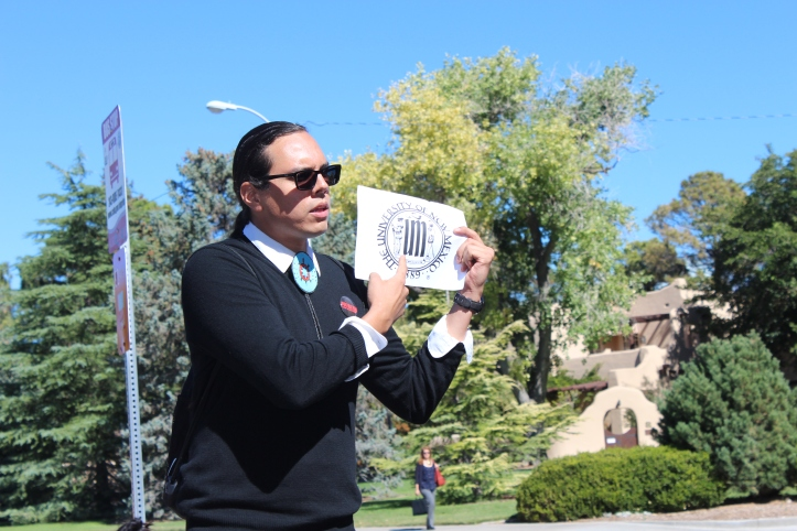 "The tour then moved to Dane Smith Hall, which was built on the former home of the Kiva Club and a building that housed the Chicano Students' Association. ""Where are the indigenous spaces on this campus?"" asked tour co-organizer Nick Estes. He pulled out a copy of the seal of the University of New Mexico and told marchers ""to really look at this seal. It celebrates the genocide of indigenous people."""