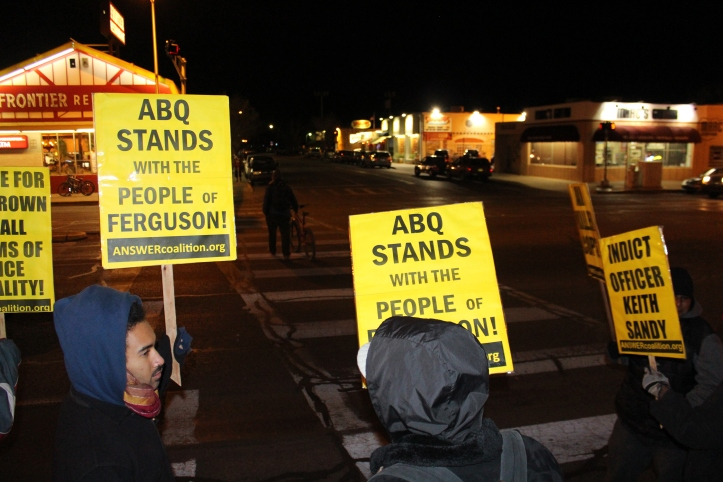People from Albuquerque began assembling along Central Avenue on the campus of UNM at 6PM in anticipation of a St. Louis press conference to announce whether a grand jury would indict Darren Wilson, a White police offcer, for the killing of Michael Brown, an unarmed Black teenager. Despite the cold temperature and  the delayed press conference, a small but growing rally stood in solidarity with Ferguson, MO.