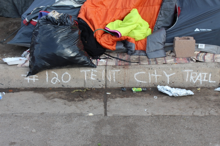 In response to the City's claim that Tent City had to move in order to make room for an urban pedestrian shopping trail between downtown and the railyard, residents of Tent City, chalked addresses on the curb in front of each Tent.